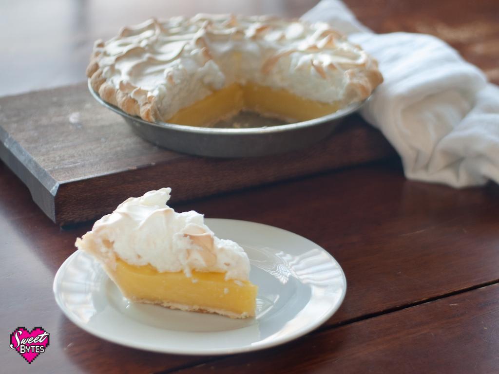 Slice of lemon meringue pie in the foreground with a whole sliced lemon meringue pie in the background for lemon meringue pie recipe