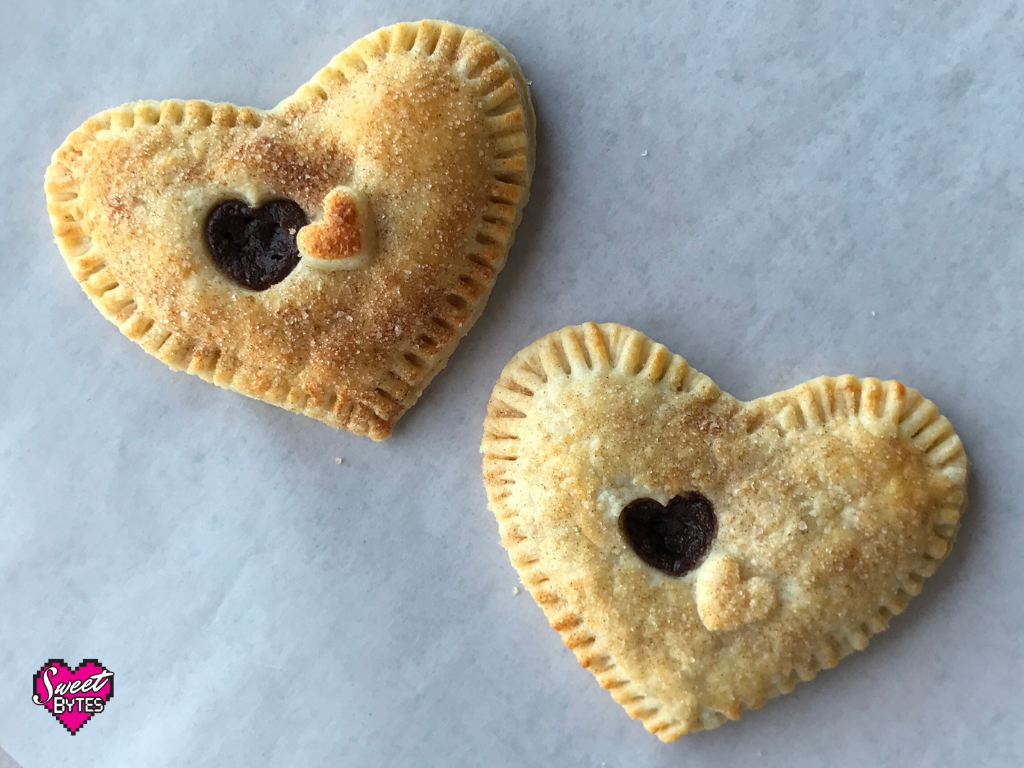 Two baked heart-shaped hand pies arranged on a white parchment paper.