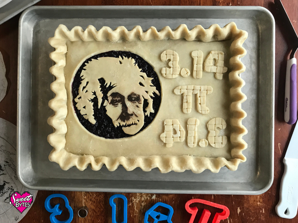 Unbaked rectangular pie with Albert Einstein's face on it. The numbers 3.14 are written in pie crust cut out numbers, then again backwards as the word pie also cut out of pie crust
